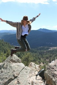 woman jumping atop mountain